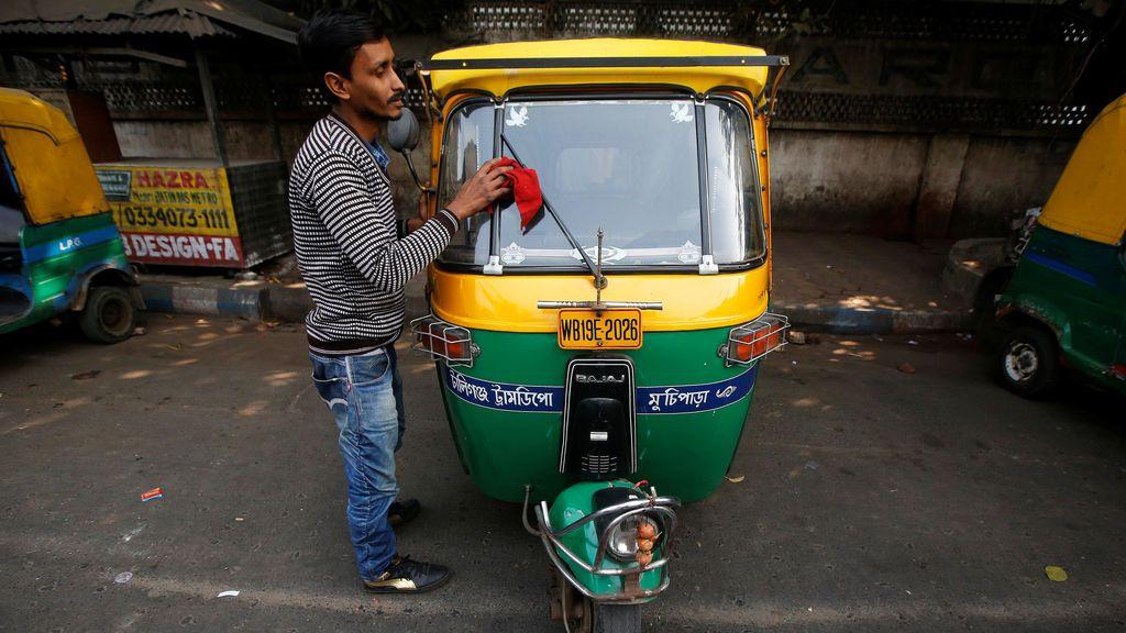 Un conductor limpia su auto Bajaj en un estacionamiento en Kolkata, India