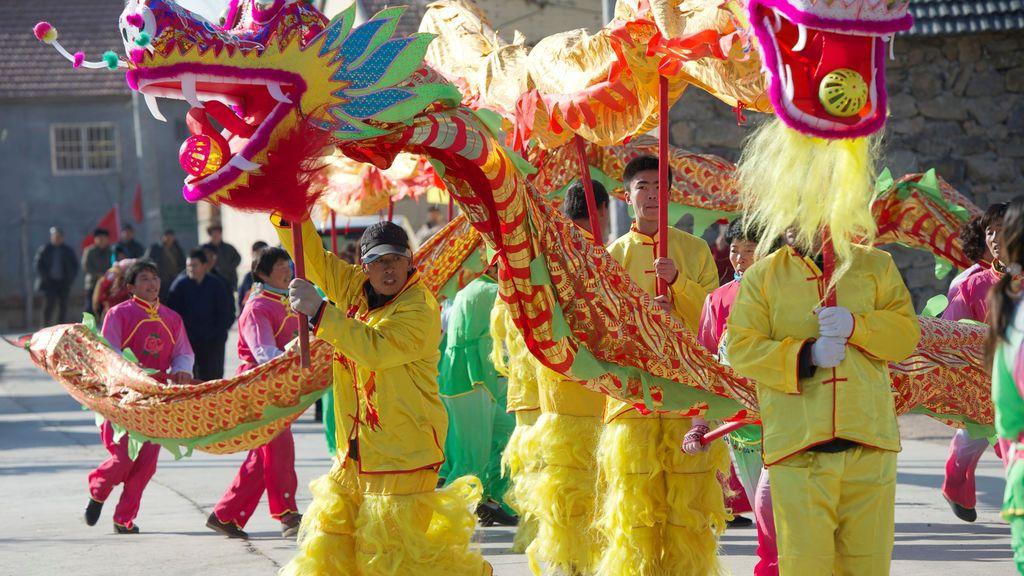 Varias personas realizan la danza del dragón durante un festival popular antes del Año Nuevo Lunar chino