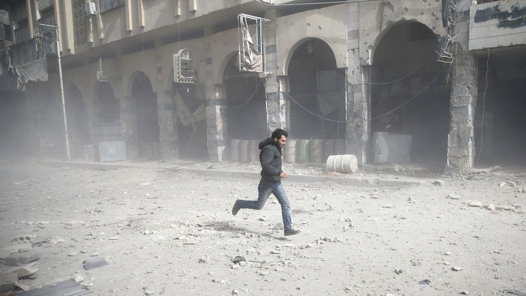 Un hombre corre tras un ataque aéreo en la ciudad asediada de Douma, en el este de Ghouta, en Damasco, Siria