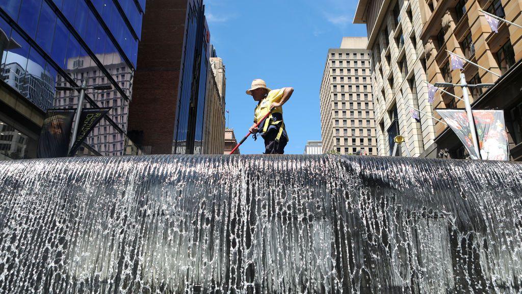 Un trabajador limpia una fuente de agua en el distrito central de negocios de Sydney (CBD) Australia