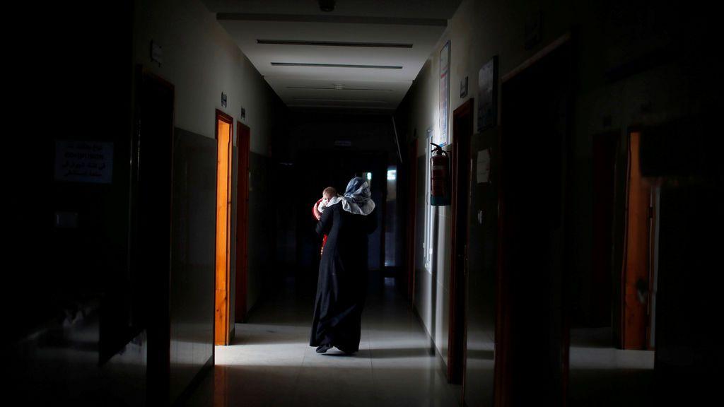 Una mujer palestina lleva a su hijo enfermo mientras camina por el pasillo en el hospital de Durra, en la ciudad de Gaza