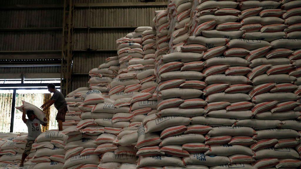 Los trabajadores cargan un saco de arroz en un almacén en la ciudad de Quezon, en el área metropolitana de Manila, Filipinas