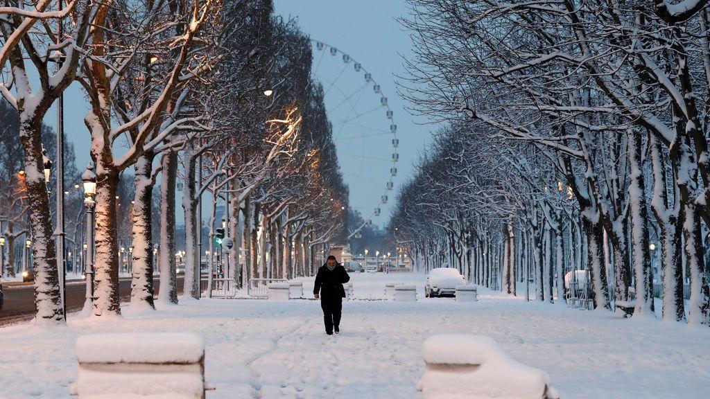 Un hombre camina por la nevada avenida de los Campos Elíseos, en París