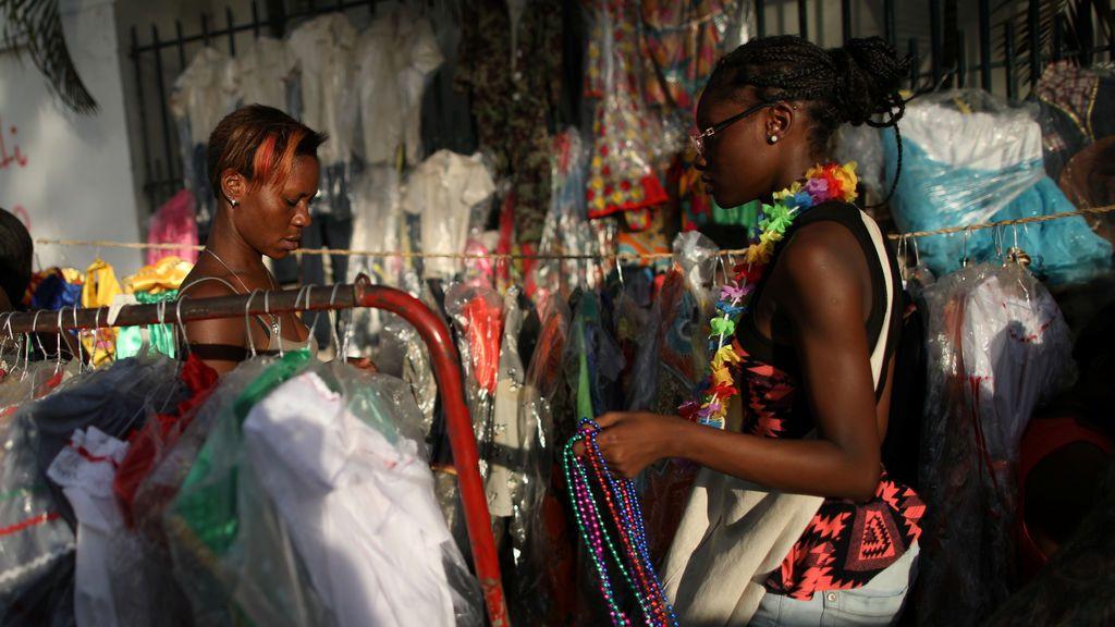 Las mujeres buscan productos en puestos con trajes en Port-au-Prince, Haití