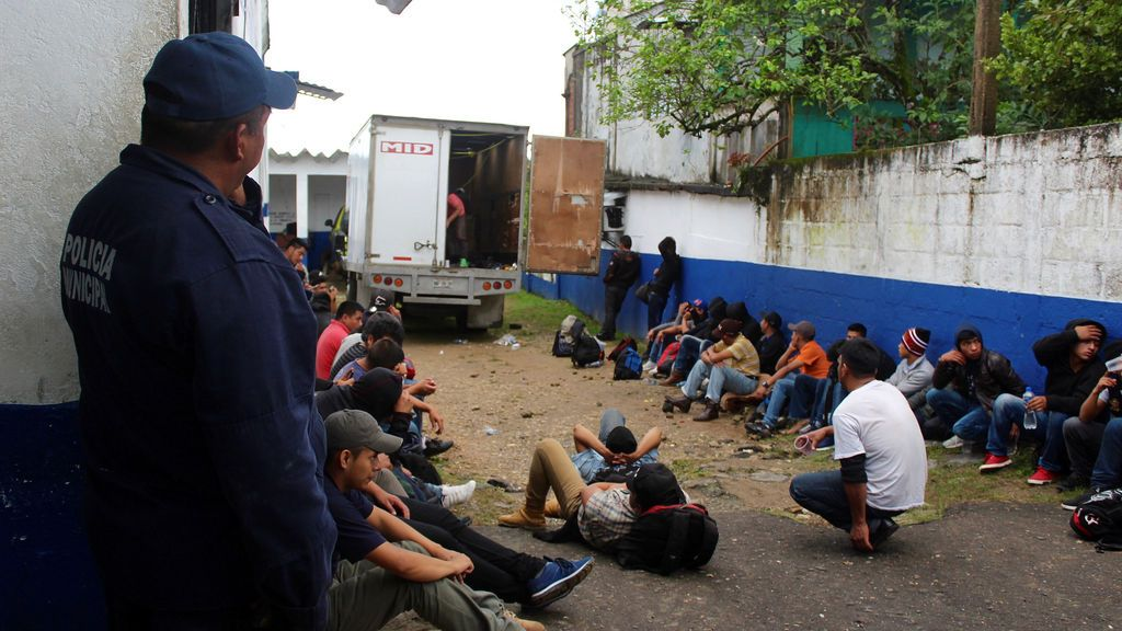 Un policía protege a migrantes de Guatemala