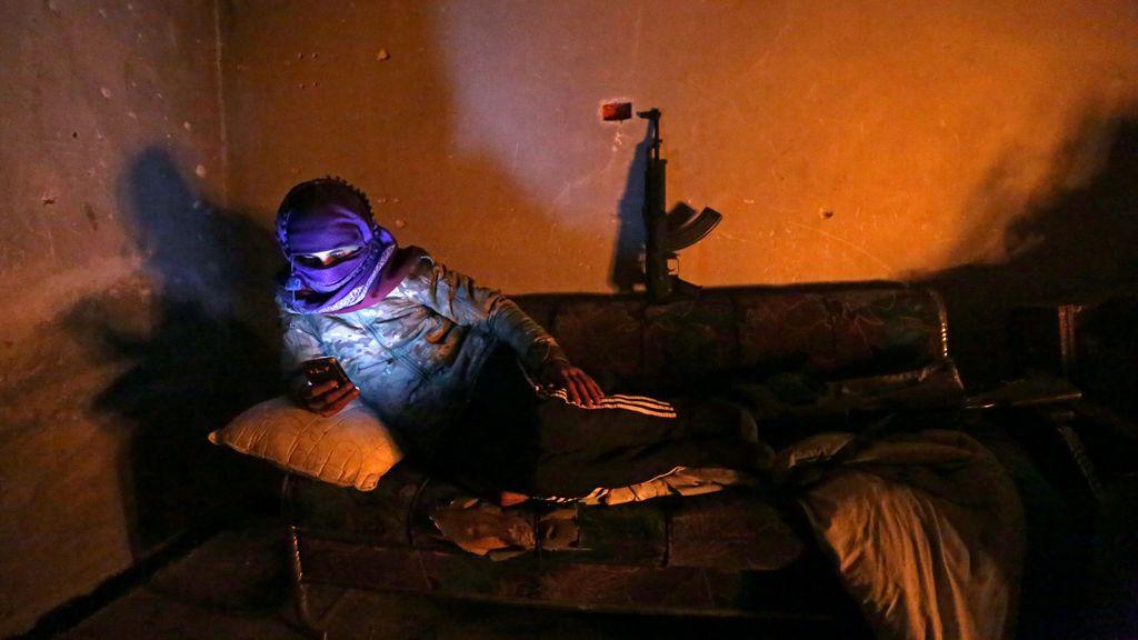 Luchador del ejército sirio libre respaldado por Turquía sostiene un teléfono móvil en la ciudad de Tadef en la provincia de Alepo, Siria