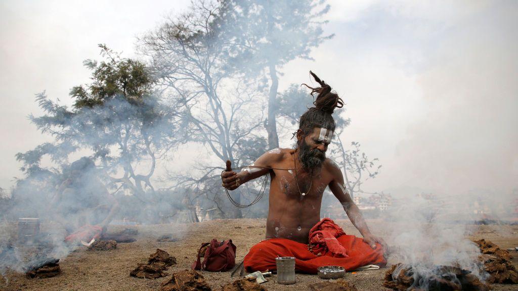 Un hombre santo hindú, o sadhu, realiza rituales religiosos en las instalaciones del templo de Pashupatinath durante el festival de Shivaratri en Katmandú, Nepal