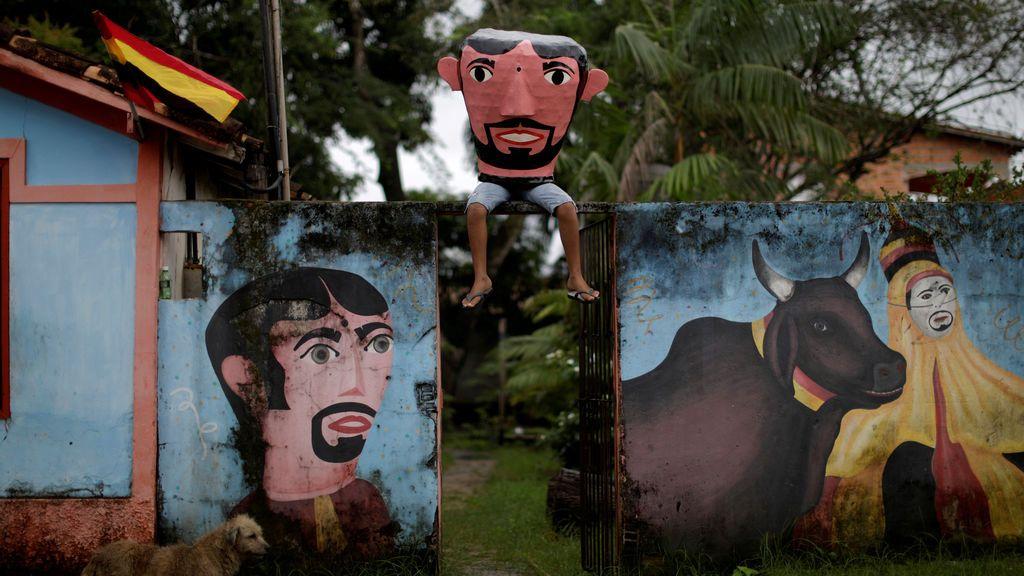 """Un miembro del """"Grupo Boi Faceiro"""" usa una máscara conocida como """"Cabecudos"""" y posa para una foto durante las festividades de carnaval en Sao Caetano de Odivelas, Brasil"""