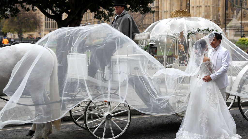 Una novia y un novio se paran junto a un carruaje tirado por caballos frente al Palacio de Westminster en el centro de Londres, Inglaterra