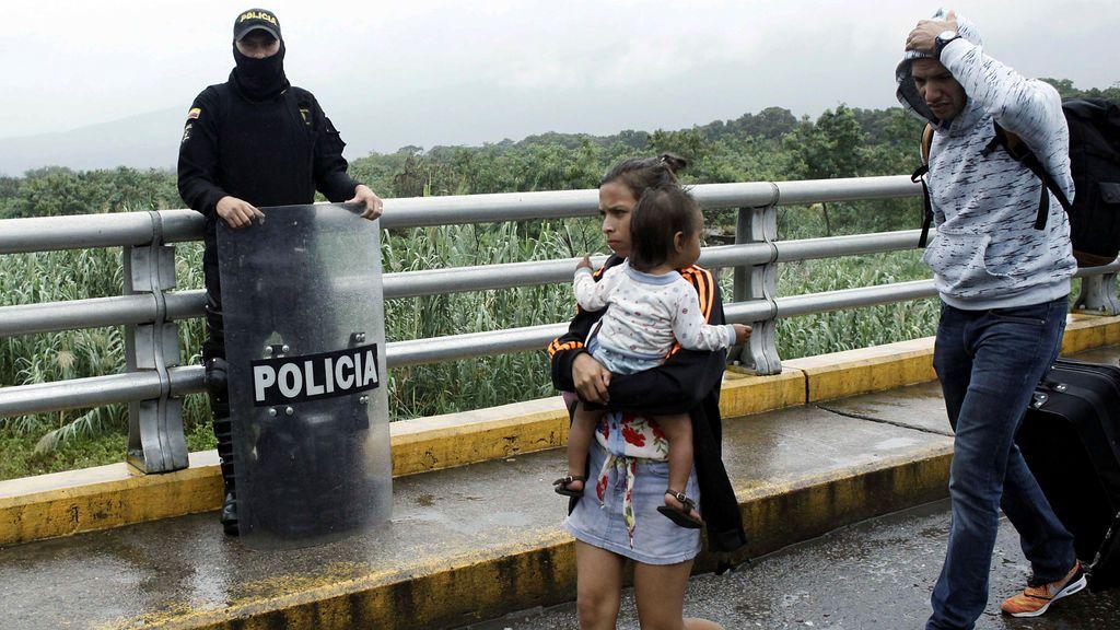 Una mujer que lleva a un niño pasa frente a un policía colombiano después de cruzar desde Venezuela el puente internacional Simón Bolívar en Cúcuta, Colombia