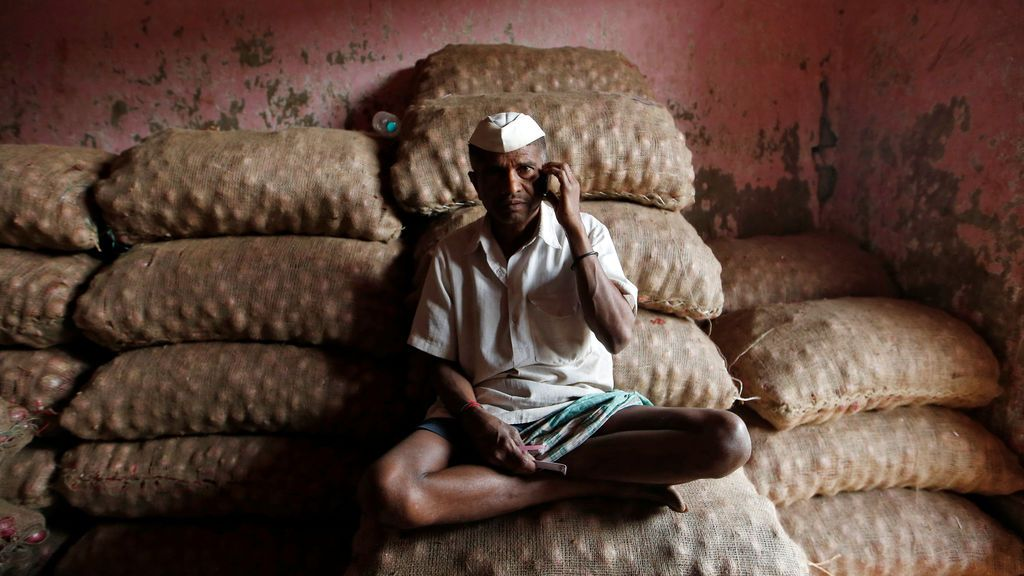Un trabajador habla por su teléfono móvil mientras se sienta en sacos de cebollas en un mercado de Mumbai, India