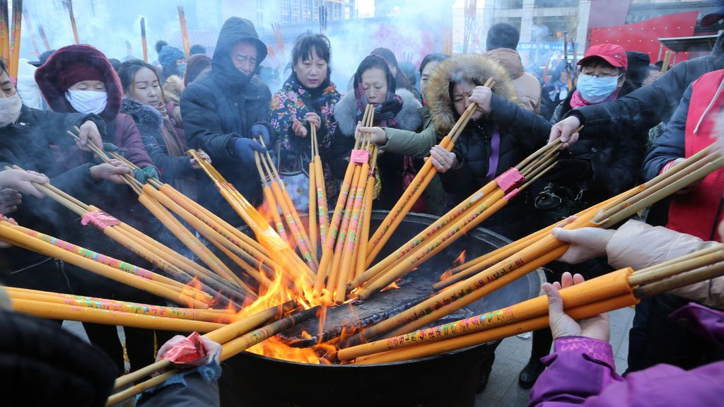 Quema de varillas de incienso y rezos por la buena fortuna en el Templo Shisheng el primer día del Año Nuevo Chino en Shenyang, China,