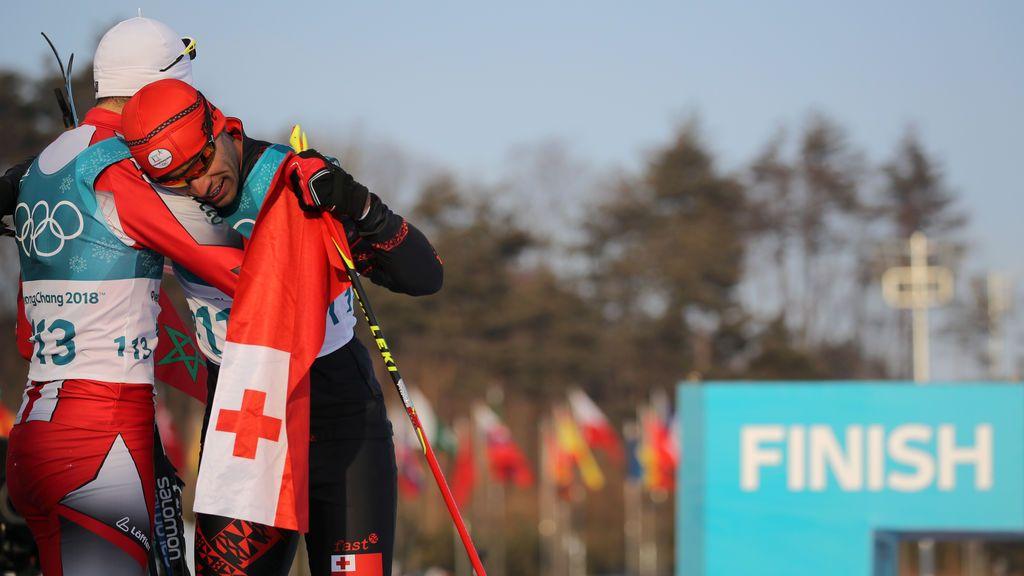 Los deportistas Pita Taufatofua de Tonga y Samir Azzimani de Marruecos se abrazan en los Juegos Olímpicos de invierno