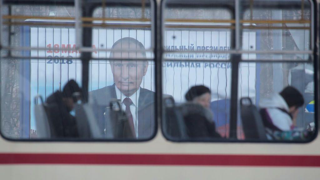 Un tranvía más allá pasa por delante de un anuncio de la campaña del presidente ruso, Vladimir Putin, antes de las próximas elecciones presidenciales, en una calle de San Petersburgo, Rusia