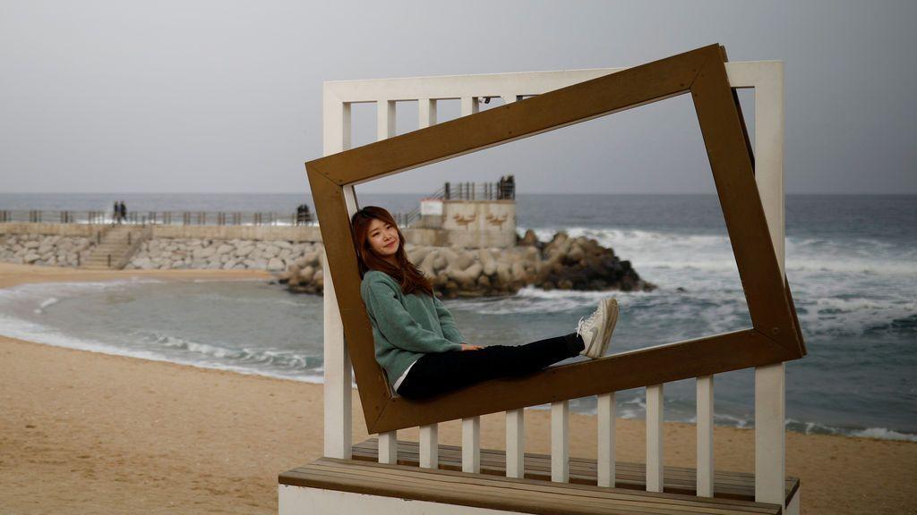 Una mujer posa para fotografías en un lugar de fotos en una playa en Gangneung, Corea del Sur