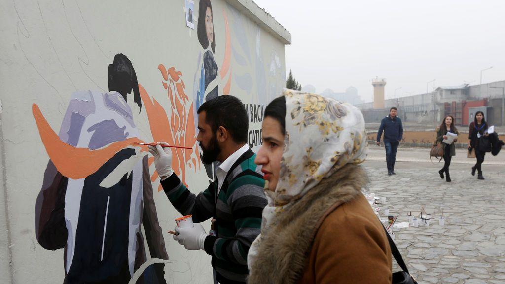 Afganos pintan un mensaje en una pared en la Universidad Americana de Afganistán en Kabul