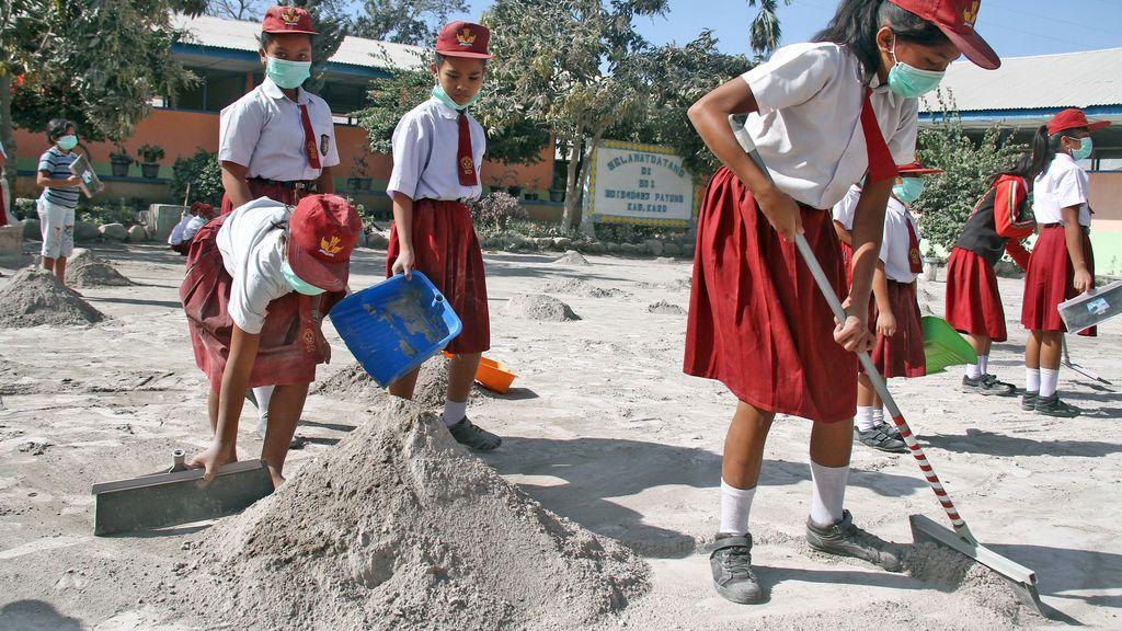 Los estudiantes limpian las cenizas del patio de su escuela después de que el volcán Monte Sinabung entrara en erupción en la aldea de Payung en Karo, Sumatra del Norte, Indonesia