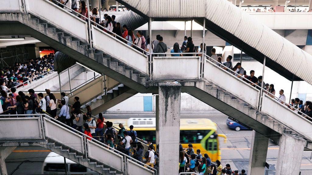 Los viajeros esperan en la cola para tomar el Metro Rail Transit en Manila, Filipinas