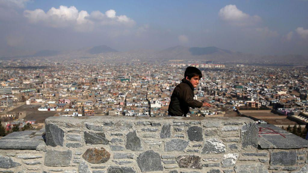Un niño camina en la cima de una colina con vistas a Kabul, Afganistán