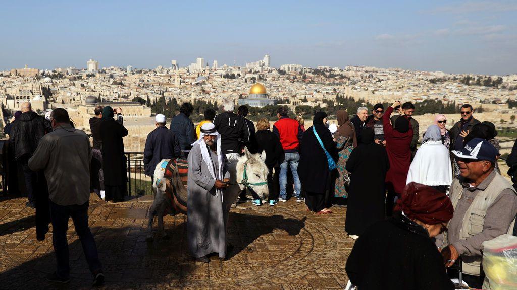 Un hombre camina con un burro mientras varios turistas se hacen fotos en el mirador del Monte de los Olivos con vistas a la Ciudad Vieja de Jerusalén