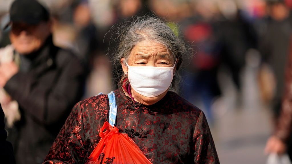 Una mujer, con mascarilla, camina por la estación ferroviaria de Beijing, China