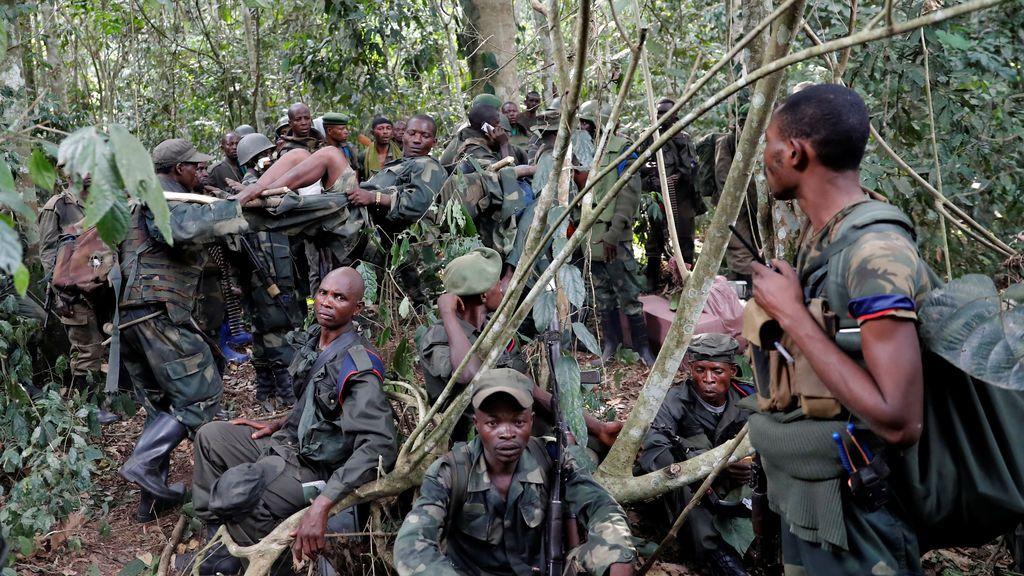 Un soldado congoleño herido de las Fuerzas Armadas de la República Democrática del Congo (FARDC) es llevado por otro soldado en el bosque después de que el ejército tomara el control de un campamento rebelde de ADF, cerca de la ciudad de Kimbau, provincia de Kivu del Norte, República Democrática del Congo