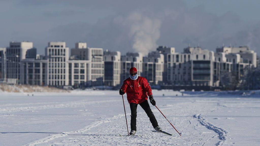 Un hombre esquia sobre el canal de remo cubierto de hielo en la ciudad de San Petersburgo, Rusia