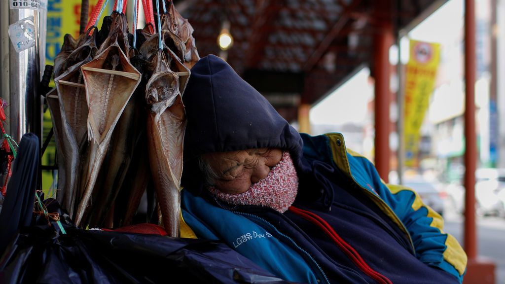 Un vendedor duerme en un mercado local en Gangneung, Corea del Sur