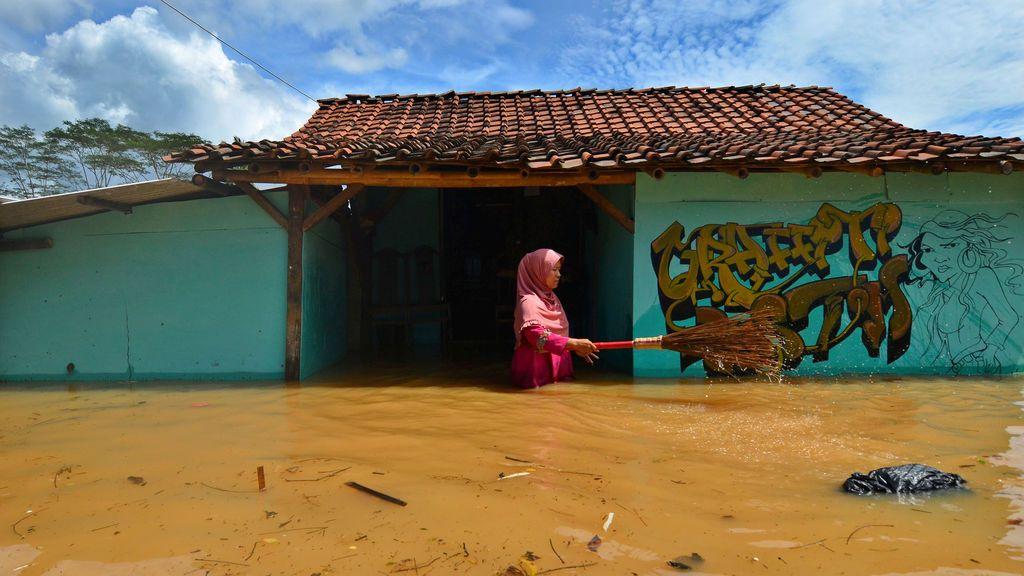 Una aldeana limpia la basura en frente de su casa tras una inundación en la aldea de Tanjungsari en Tasikmalaya, Indonesia