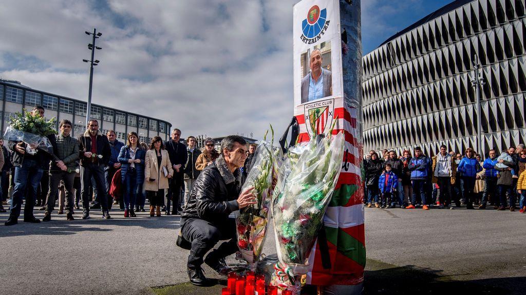 Un hombre deposita una corona de flores durante la concentración por el ertzaina fallecido