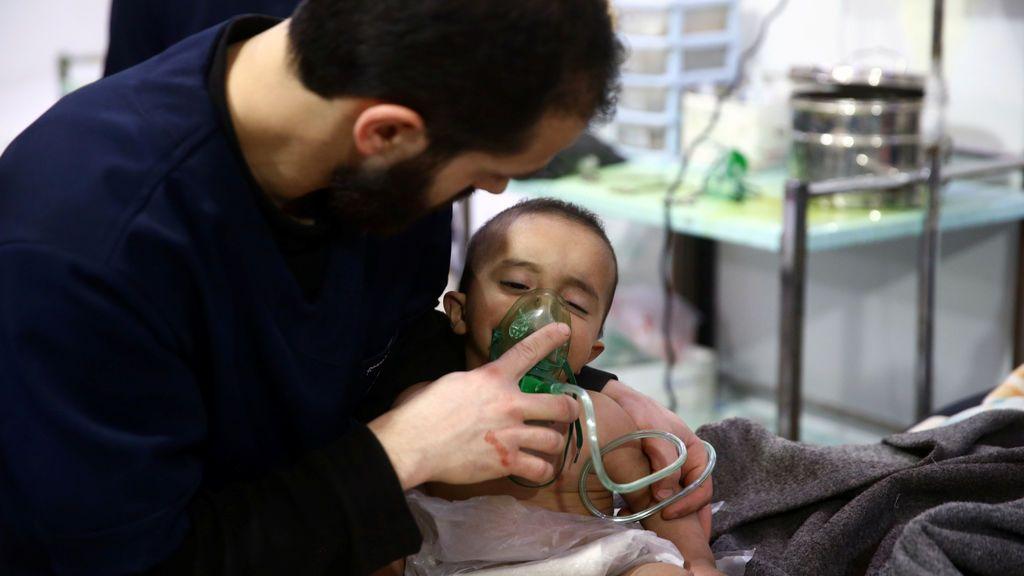 Un hombre asiste a un bebé en un centro médico en Douma, Ghouta Oriental, Damasco, Siria