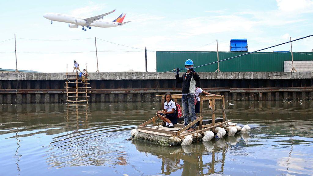 Un hombre agarra una cuerda mientras lleva a los niños a la escuela en una balsa improvisada en la ciudad de Paranaque, al sur de Manila, Filipinas