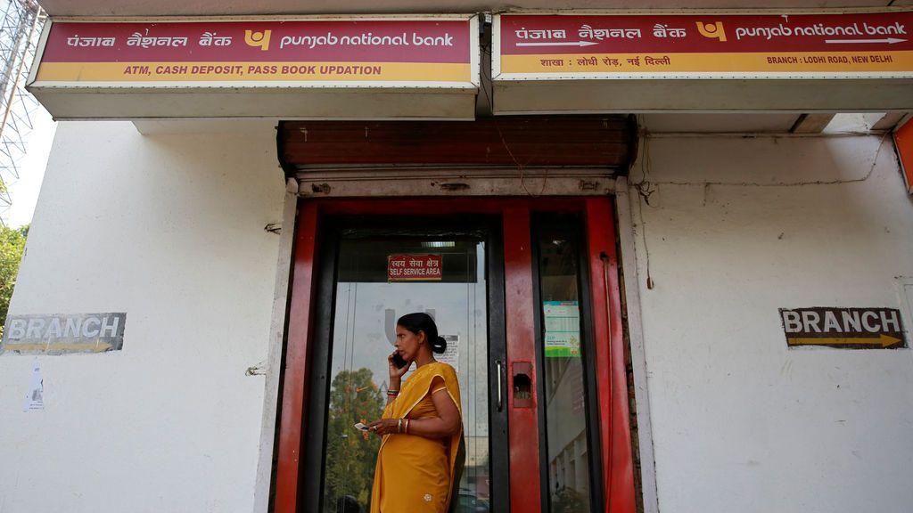 Una mujer habla por su teléfono móvil frente a una sucursal del Banco Nacional de Punjab (PNB) en Nueva Delhi, India