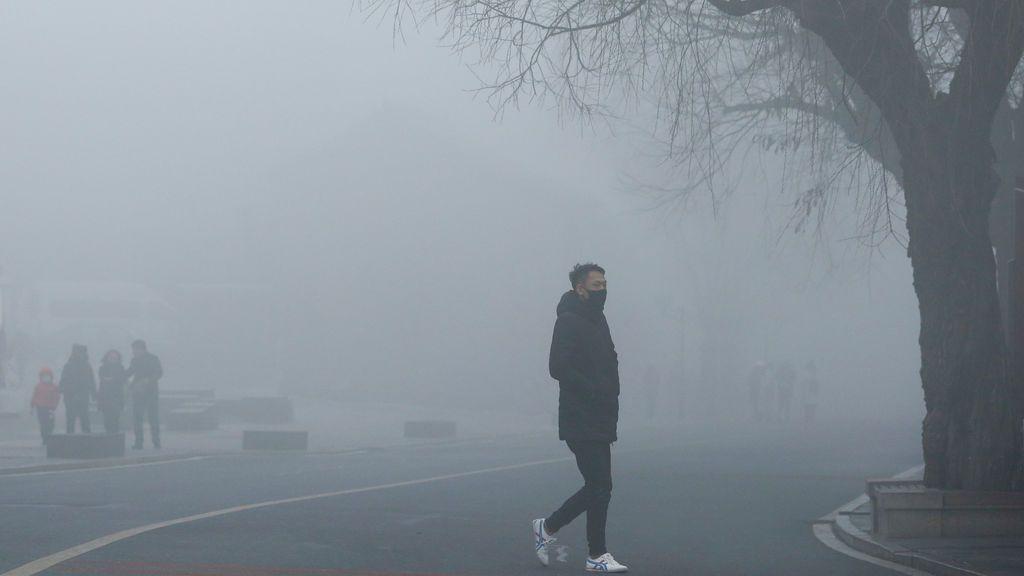 La gente camina por los alrededores de la Gran Muralla de China en un día en el que hay una gran niebla
