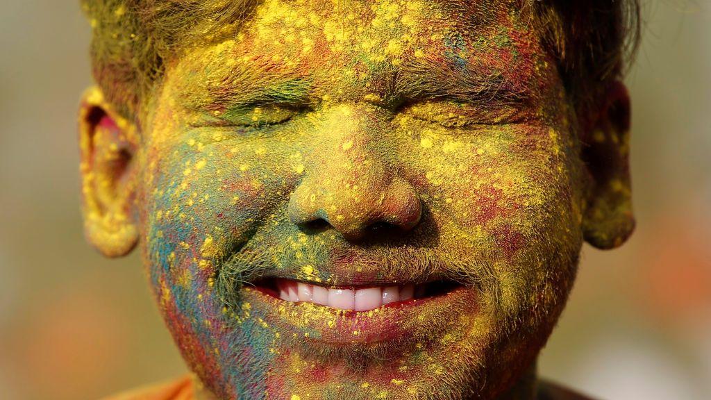 Un estudiante de la Universidad Rabindra Bharati sonríe con la cara manchada de polvo de color durante las celebraciones de la fiesta Holi dentro del campus universitario en Calcuta, India