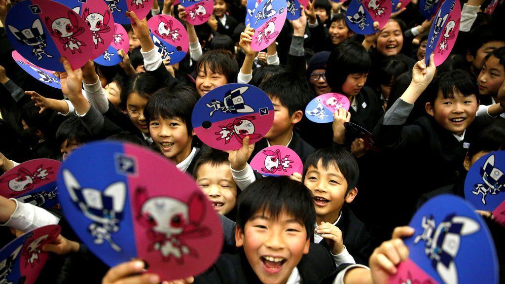 Estudiantes muestran abanicos de papel con las mascotas de los Juegos Olímpicos de Tokio 2020 después de su presentación en Tokio, Japón