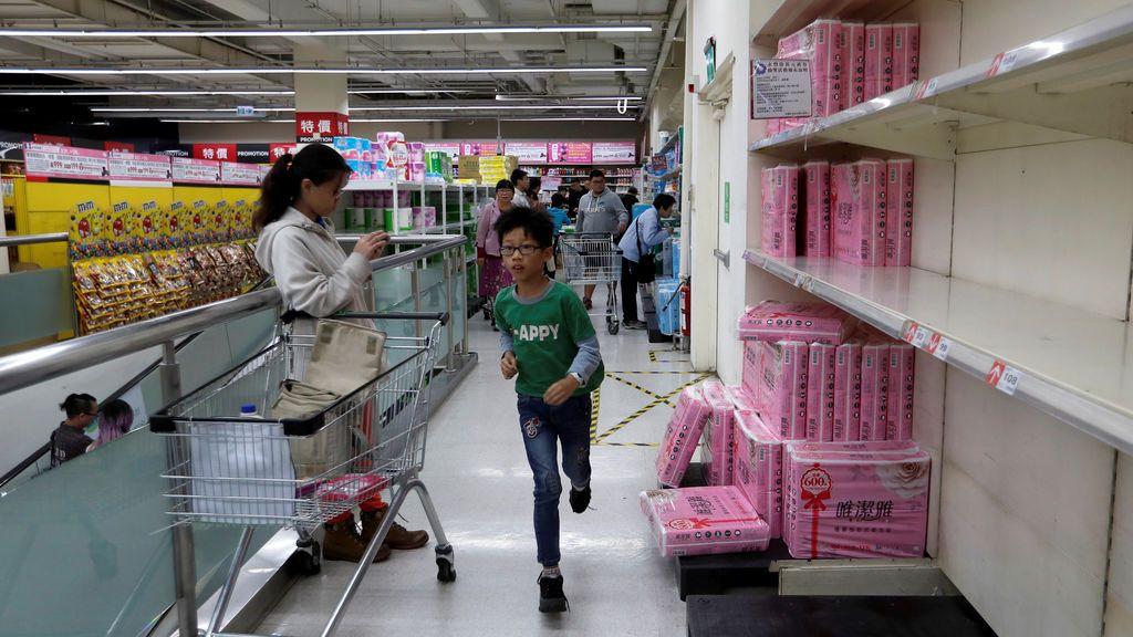 Un niño corre a por papel higiénico en un supermercado de Taiwán en el que las existencias se están acabando tras los rumores de que suban los precios