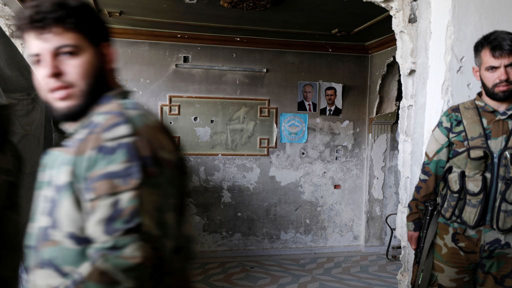 Soldados sirios leales al presidente Bashar al Assad en el interior de un edifico con fotografías de al Assad y Putin en Damasco, Siria