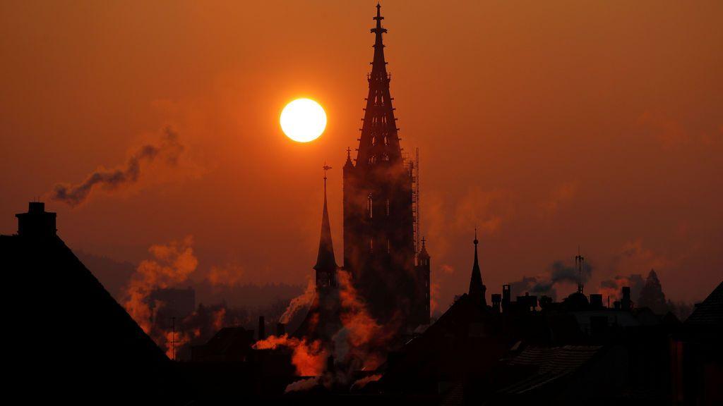 El sol sale detrás de la Catedral de Münster durante una mañana fría en Berna (Suiza) dejando una preciosa estampa
