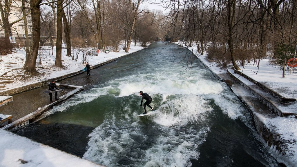 Un surfista surca una ola artificial del río Eisbach durante un día invernal en el parque del Jardín Inglés en Múnich (Alemania)