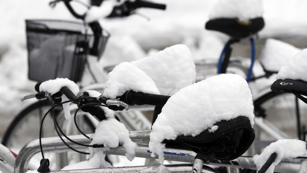 Varias bicicletas cubiertas por la nieve tras la intensa nevada caída en Pamplona