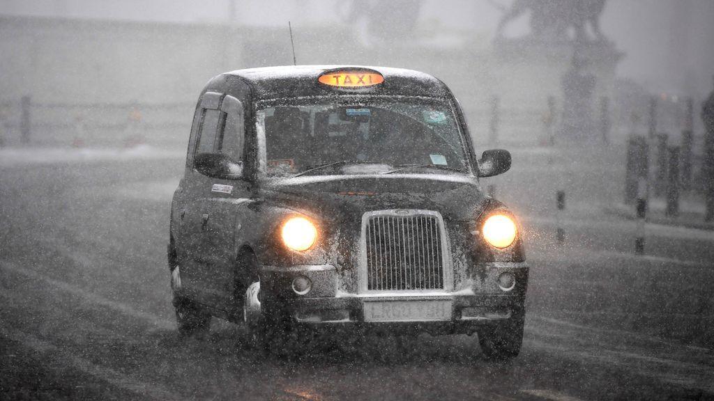 Un taxi circula por una calle cubierta por la nieve en Londres (Reino Unido)