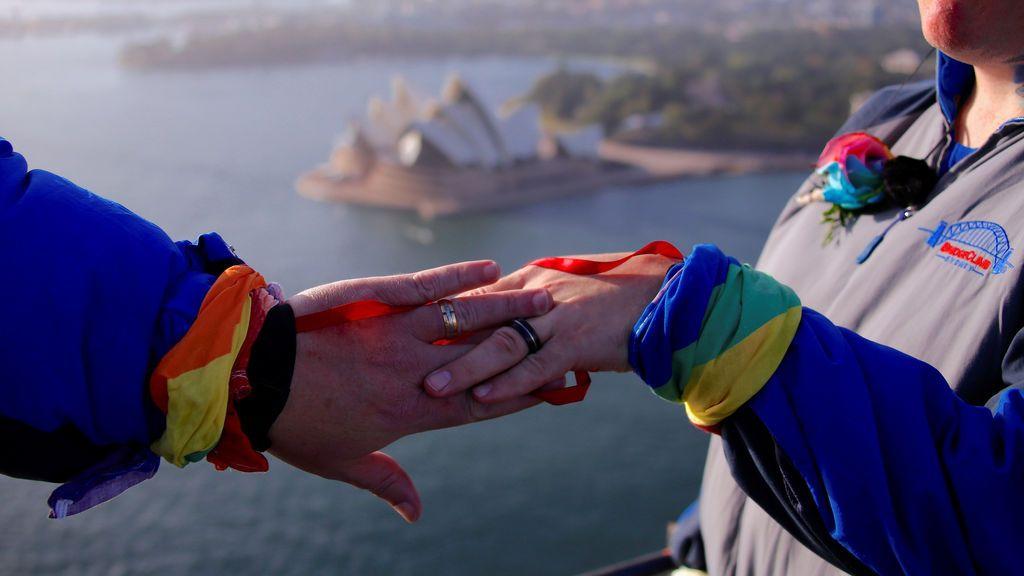 Dos mujeres exhiben sus anillos en lo alto del Sydney Harbour Bridge después de convertirse en la primera pareja del mismo sexo en casarse, en Sydney (Australia)