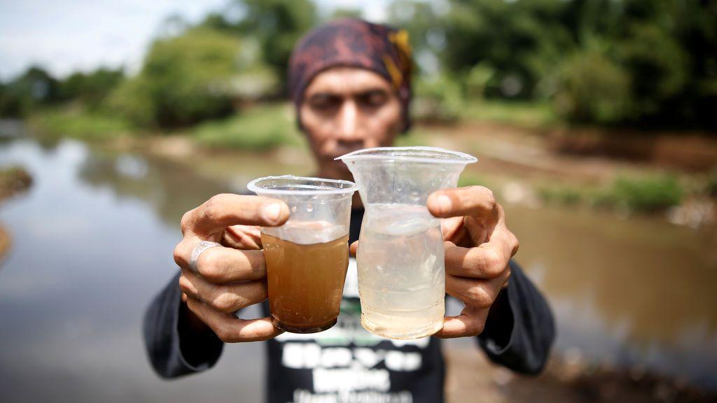Un activista ambiental sostiene un vaso de agua del río Citarum y otro de un afluente que atraviesa un área densamente poblada con fábricas textiles al sureste de Bandung, provincia de Java Occidental, Indonesia
