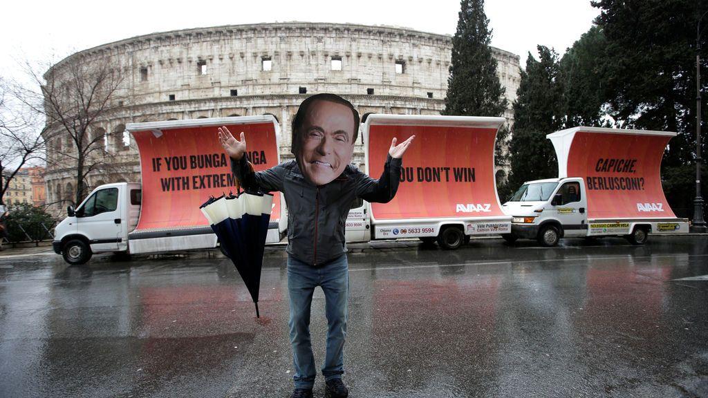 Un activista con una máscara del líder del partido Forza Italia, Silvio Berlusconi, posa en el Coliseo el día después de las elecciones parlamentarias de Italia, en Roma
