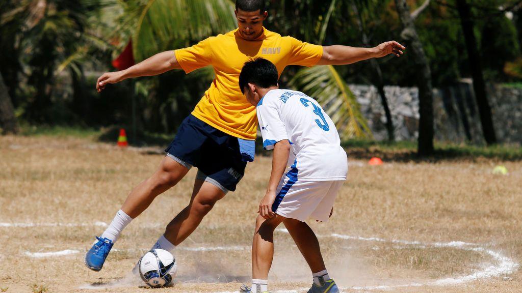 Un marinero estadounidense juega al fútbol con un niño durante su visita a la Aldea Infantil SOS Da Nang en Vietnam
