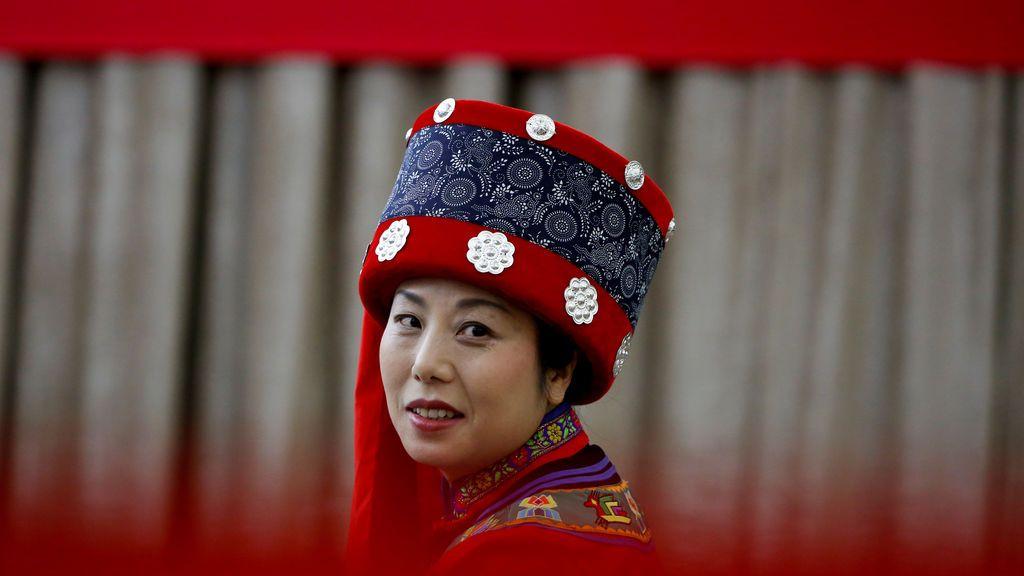 Una mujer asiste, con el atuendo tradicional, a una conferencia de prensa del municipio de Chongqing en China