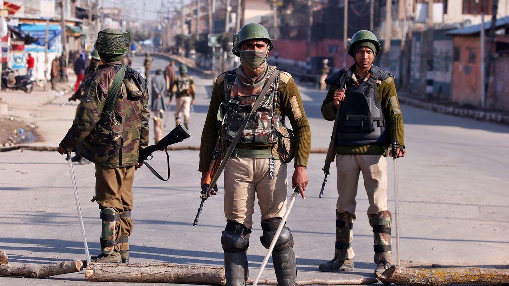 Policías indios vigilan un camino en Cachemira, Srinagar