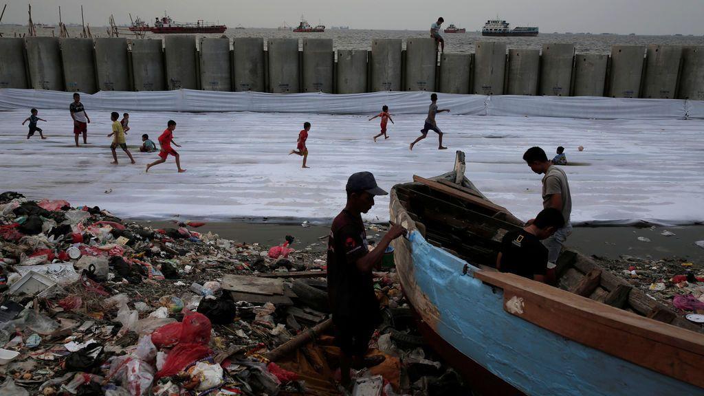 Los pescadores reparan su bote de madera mientras los niños juegan al fútbol ante la construcción de un muro de cemento en el distrito de Cilincing de Yakarta, Indonesia