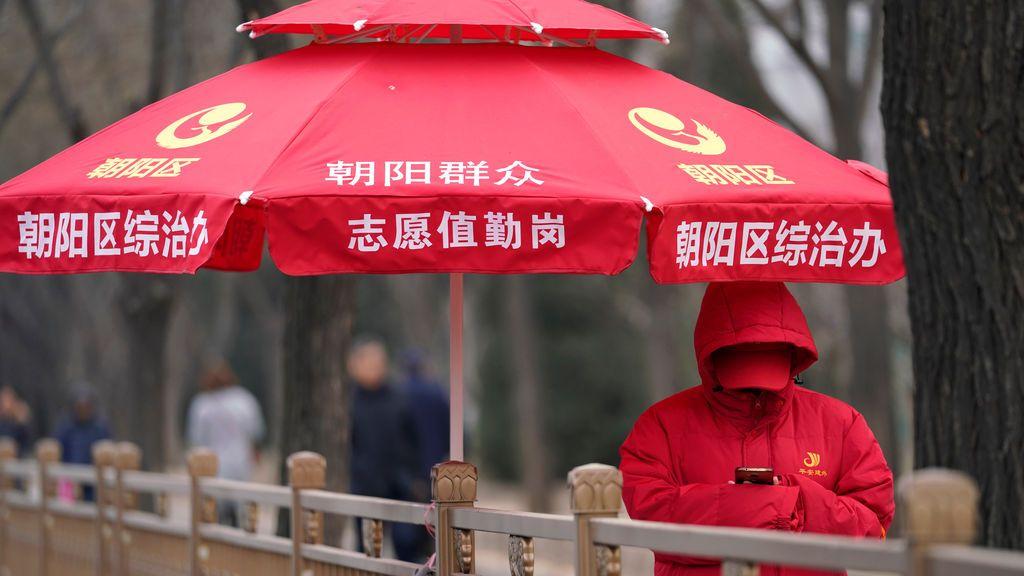 Una voluntaria mira su móvil en el centro de la ciudad china de Beijing